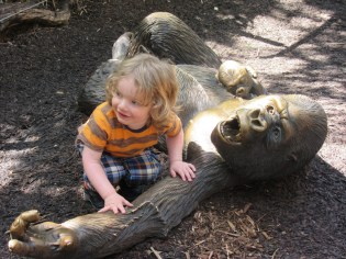 Noah playing with a gorilla statue at San Diego zoo.
