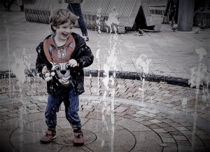 Noah plays happily in the fountains