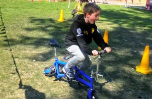 Noah tests out a very strange bike at Circus Avago, Freedom Festival.
