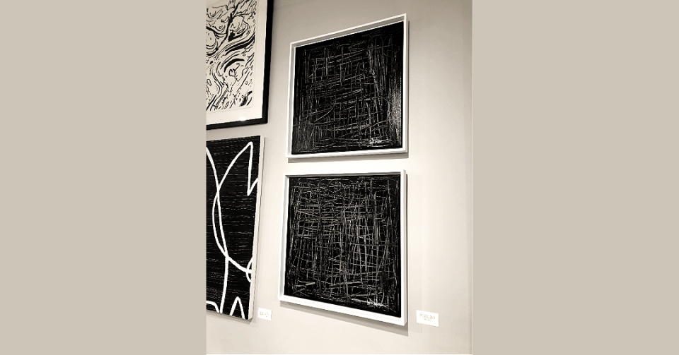 pair of square black and white paintings with white frames in showroom