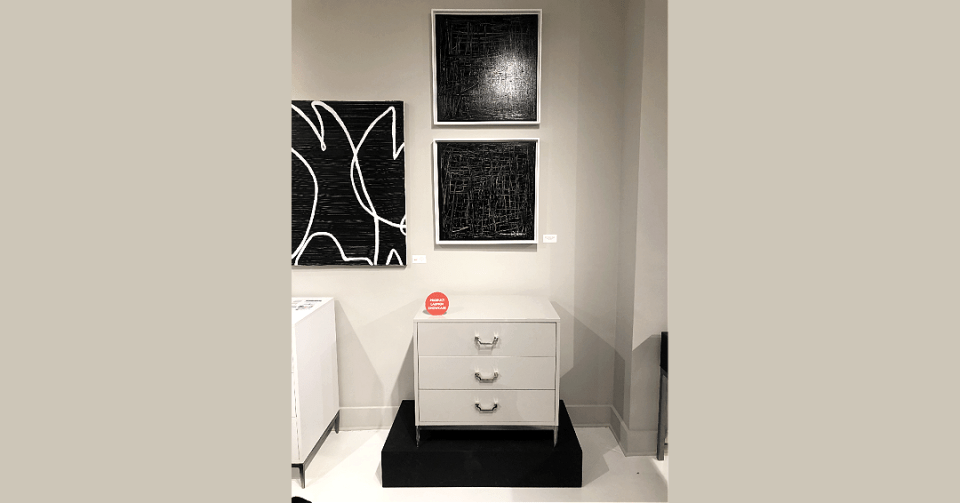pair of black and white square paintings with white frame in showroom with side table