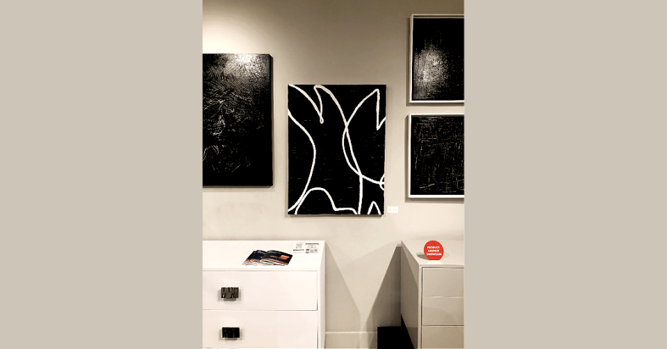 black and white abstract painting displayed on showroom wall with three black and white paintings