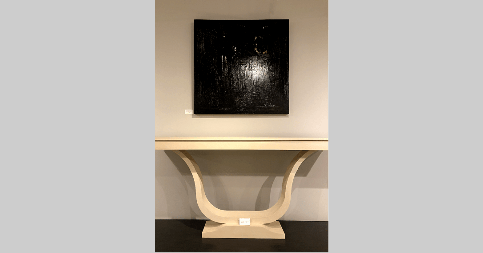 black abstract painting with white details in showroom with console