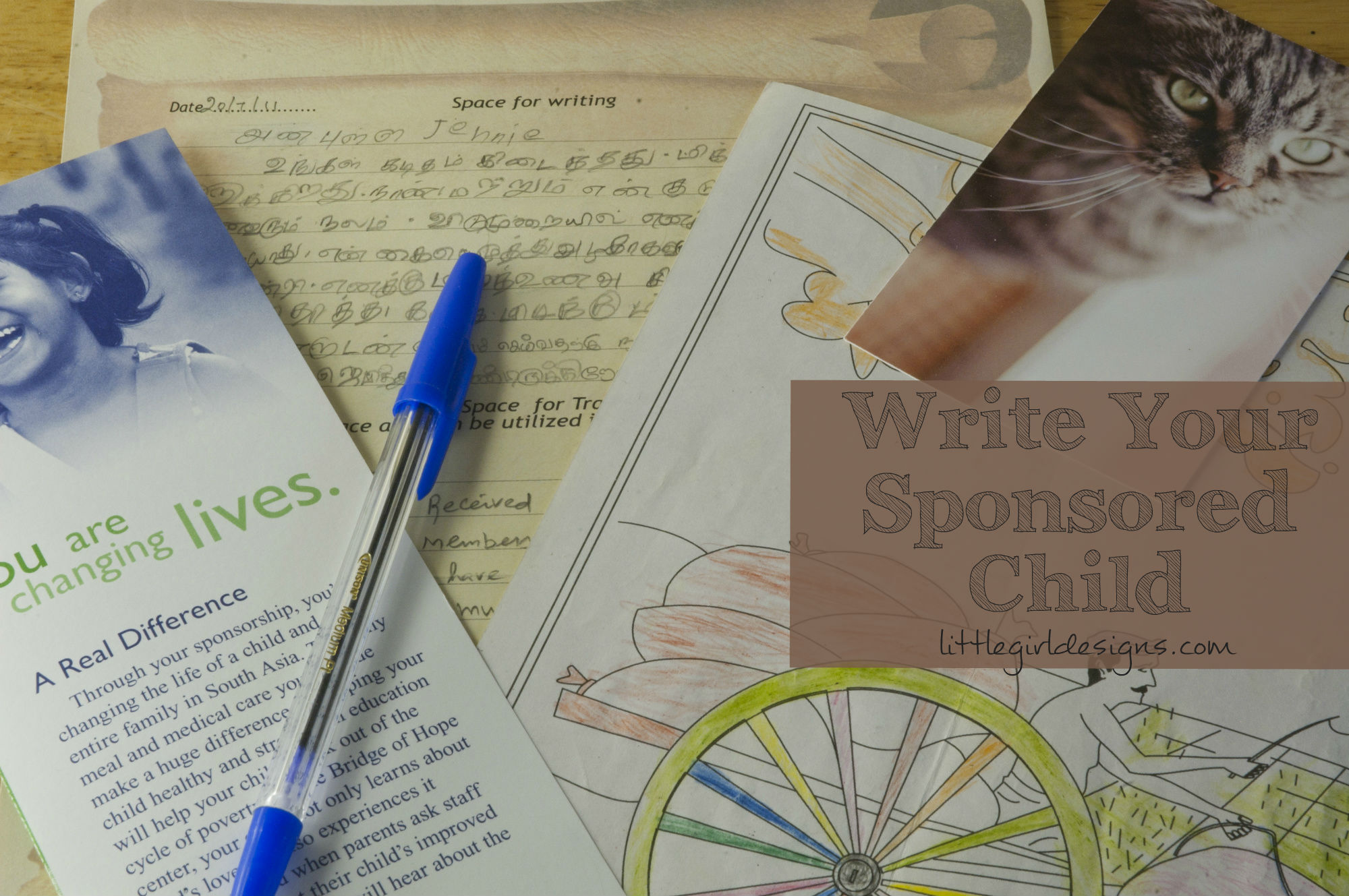 Letters from a sponsored child and a picture of a cat on a desk.