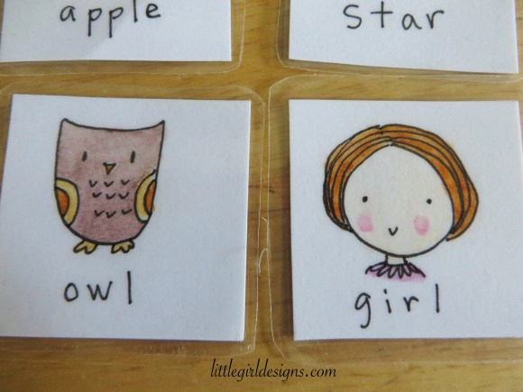 """Close up of two """"Name Game"""" cards: a sketch of an owl and of a girl."""
