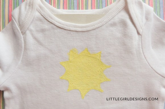 Use fabric paint, fabric markers, and embroidery floss to create a one-of-a-kind sunshine onesie for your little one. This also makes a great gift for a baby shower!