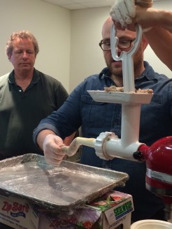Dustin shows the class how to ease the sausage mixture into the casing without tearing it
