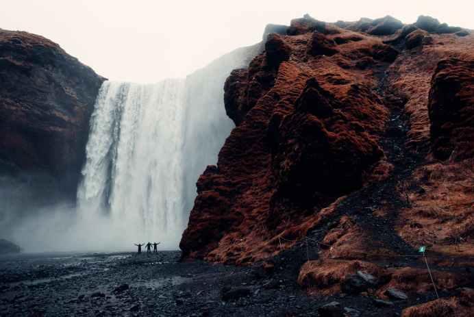 three men standing near waterfalls