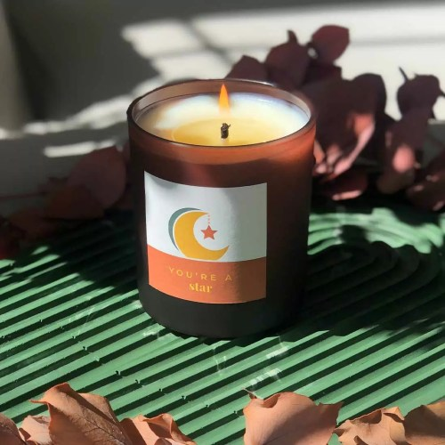 large candle with moon and star design label