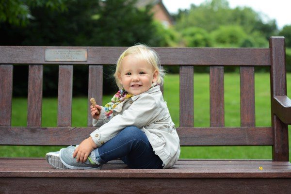 autumn little girl sitting on a bench
