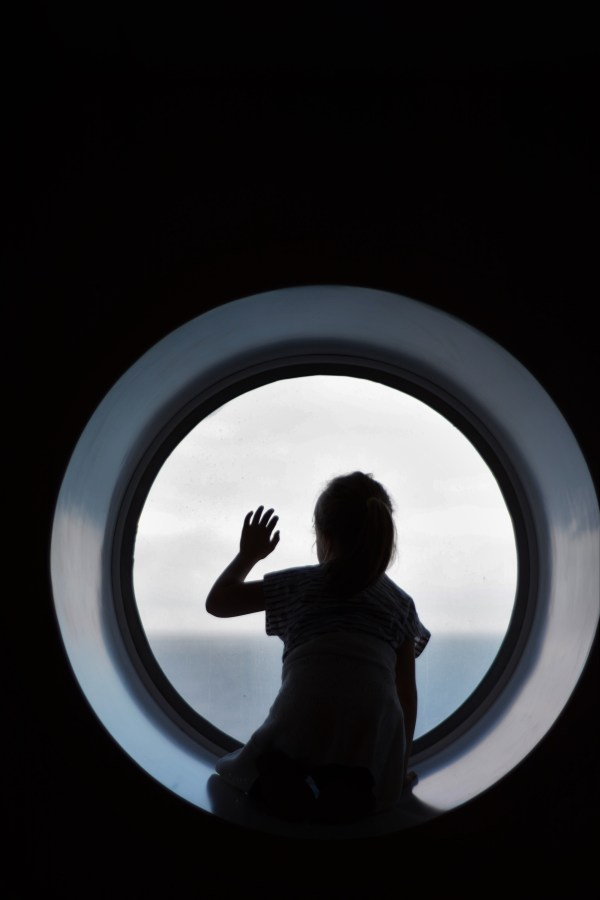 Ferry to France with Children 5 year old looking out of porthole