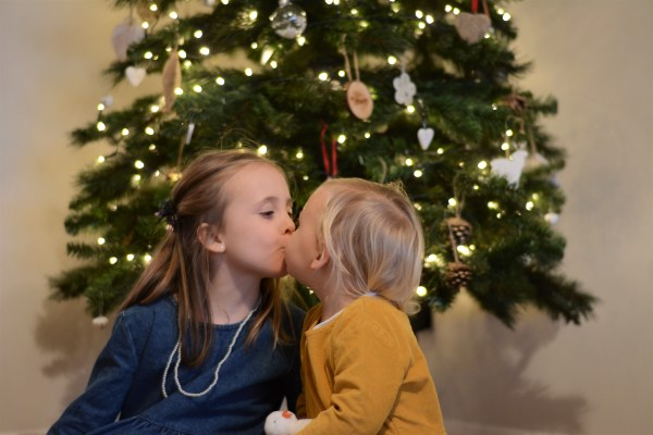 Sisters, siblings Decemberkissing in front of the christmas tree