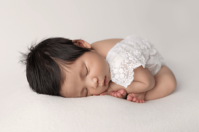 a 3 week old newborn baby laying on a blanket wearing a lace romper