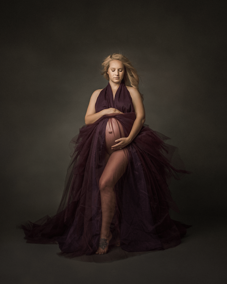 a pregnant mother wearing a purple dress during a maternity photo session