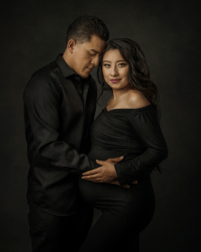 a mother and father during a maternity session wearing black clothing