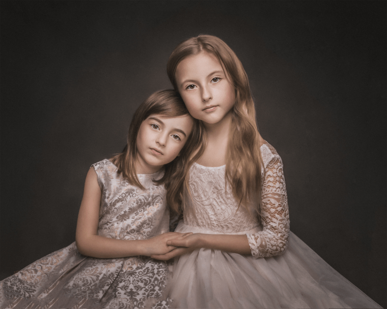 Two young sisters embracing while wearing gold and cream dresses