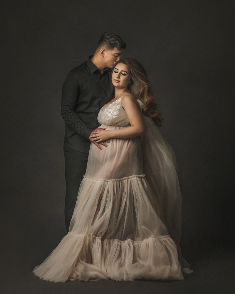 A pregnant mother embracing her husband while wearing a cream colored tulle couture dress