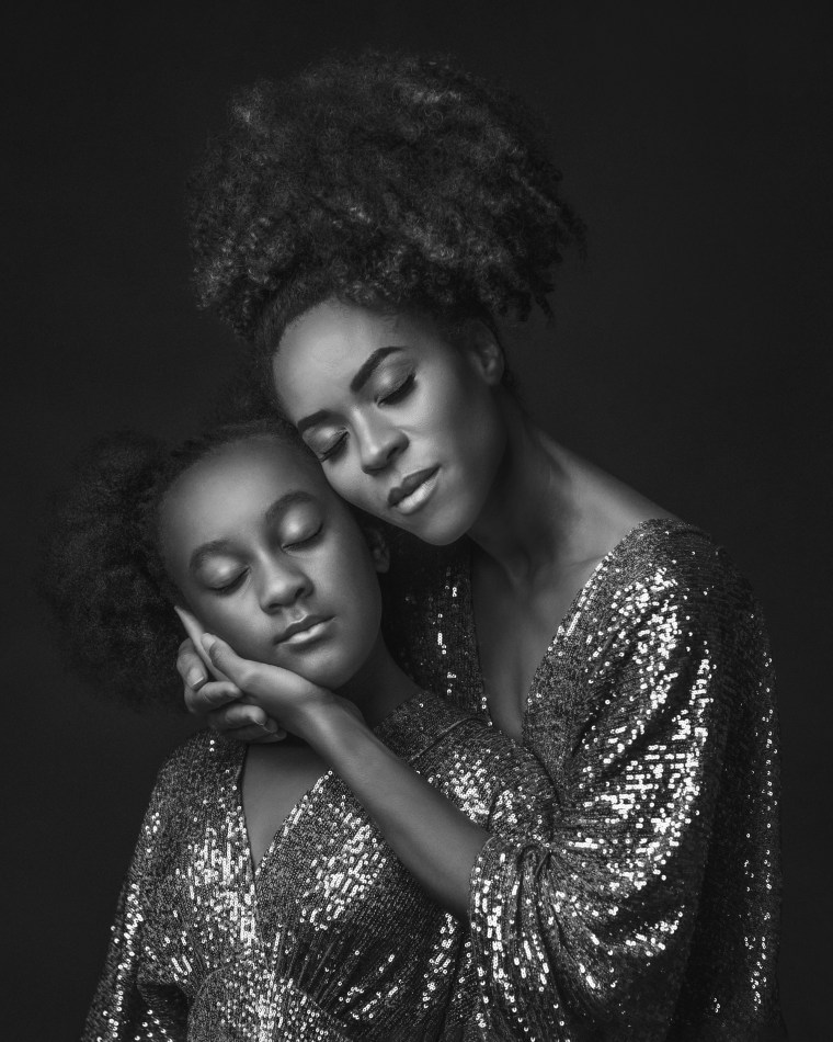 A mother embracing her young daughter while they are both wearing sequin dresses