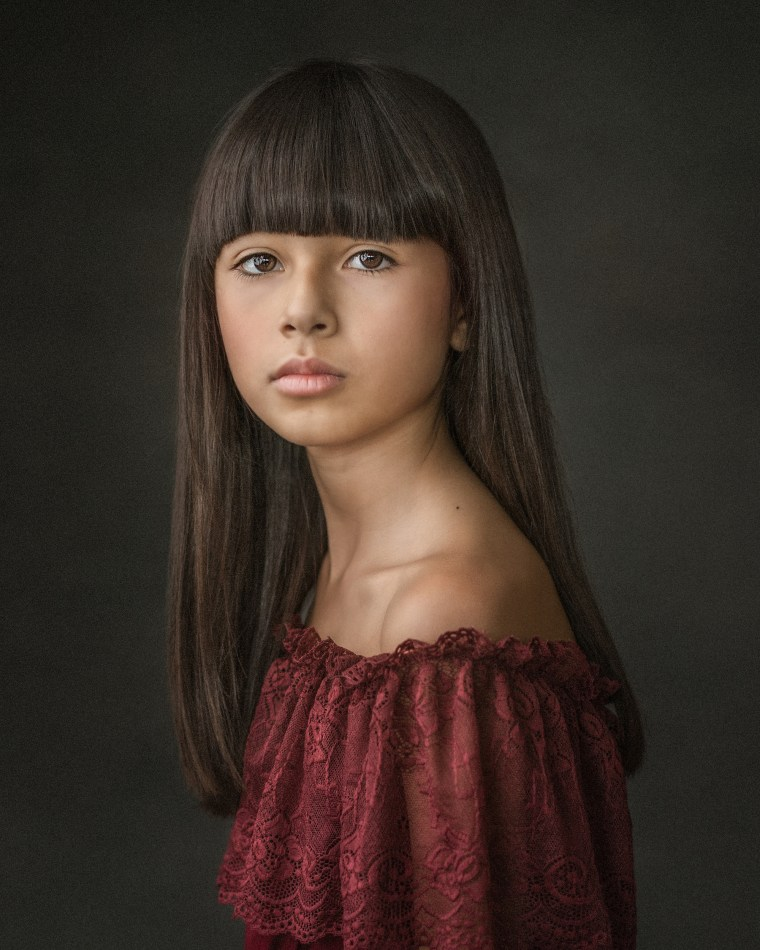 A beautiful 11 year old girl wearing a red lace dress