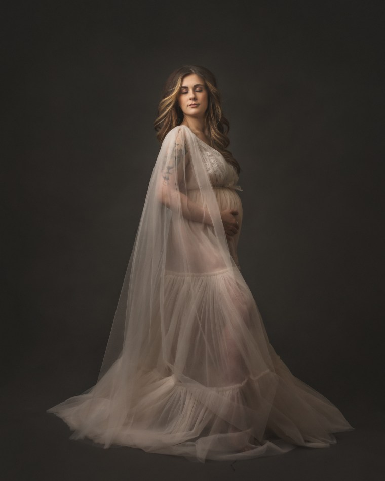 A pregnant mother wearing an ivory tulle dress embracing her belly