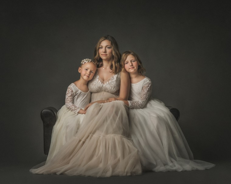A mother and her two young daughters sitting on a leather couch embracing eachother