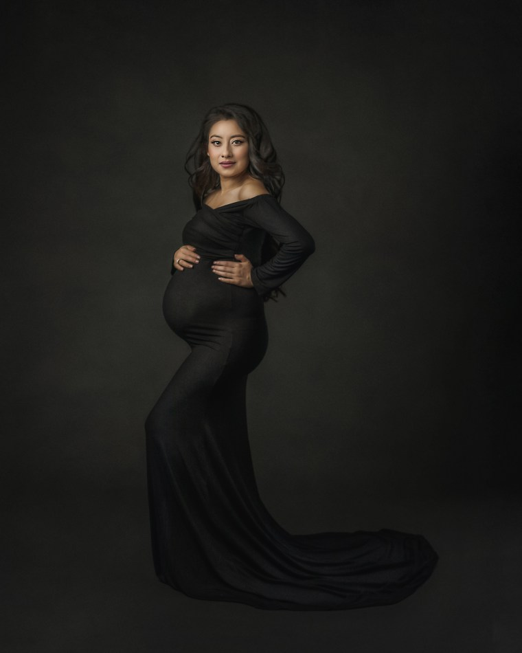 A pregnant mother wearing a long fitted black dress and embracing her belly