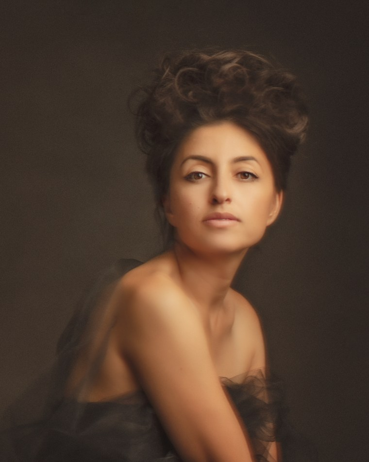 a woman with brown hair wrapped in black tulle posing in a photography studio for a creative project