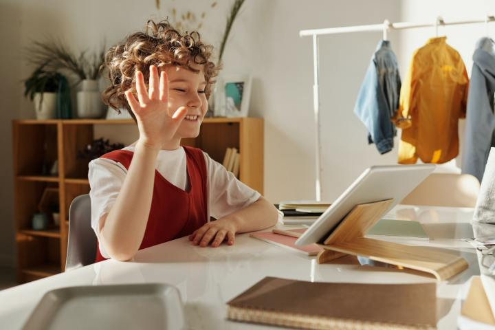 a young boy sits at a desk and waves hello to his online teacher