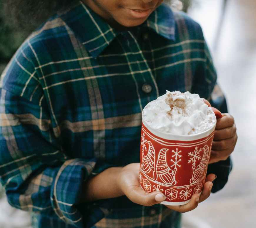 black child holding mug of hot drink with foam