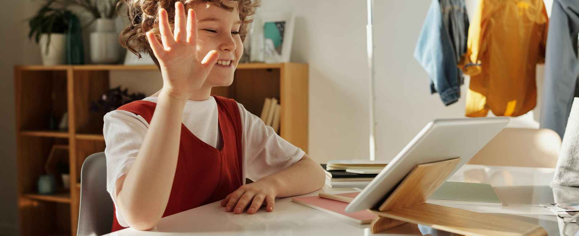 photo of child smiling while using tablet computer