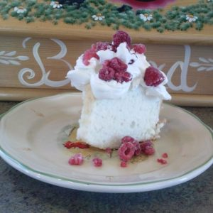 Angel food cake with real whip cream and raspberries.