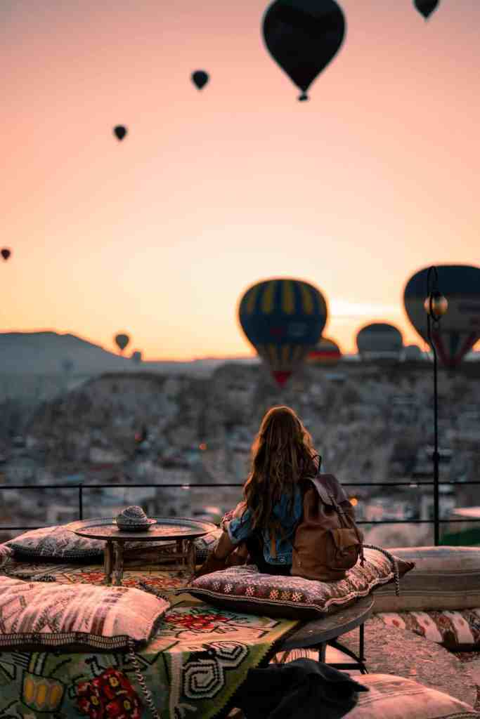 Woman watching the hot air balloons during golden hour