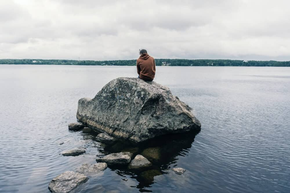 Man sitting on a rock on the sea dealing with post-travel depression