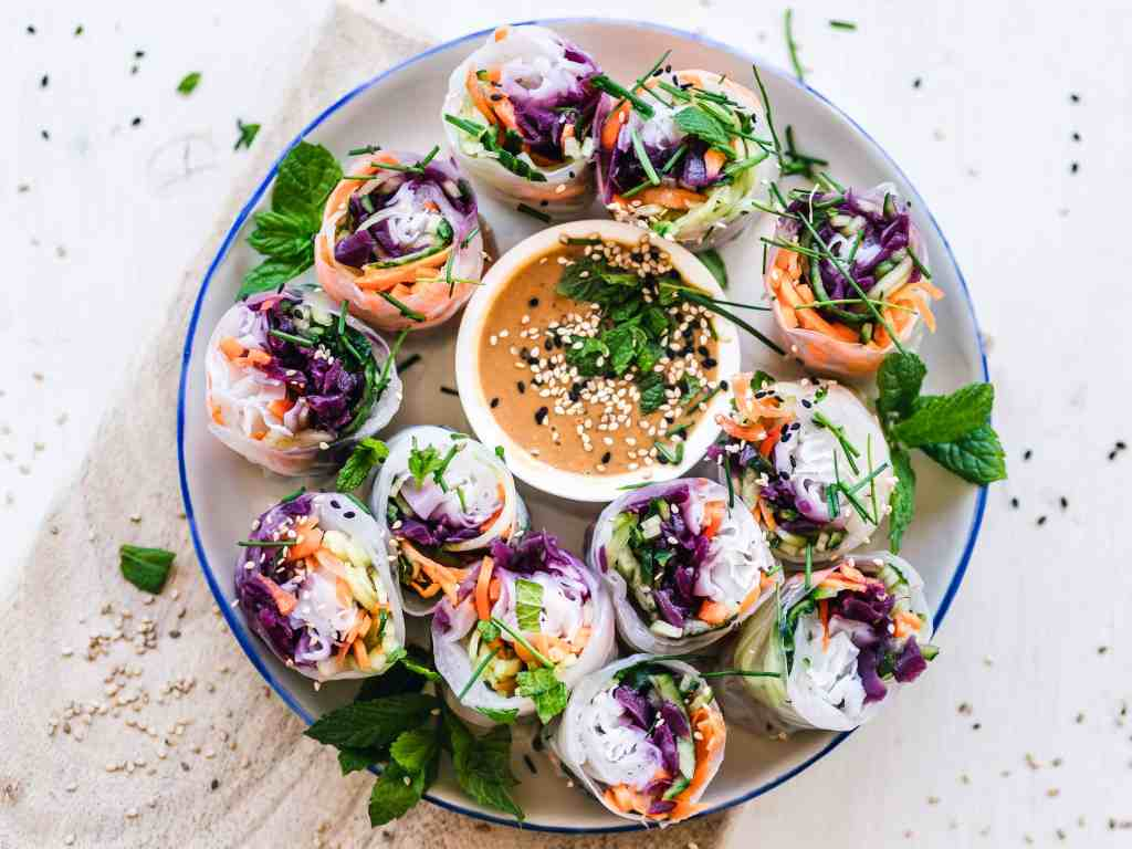 plate of colourful raw vegetables wrapped up in rice paper around a dish of dipping sauce.