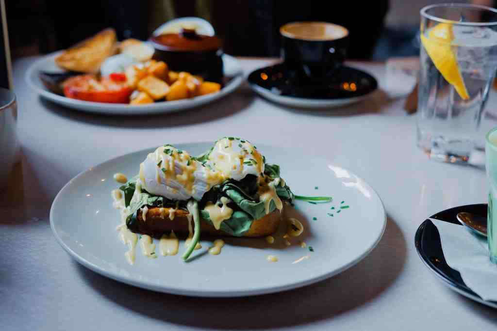 Sustainable restaurants - Eggs benedict on a white plate in the foreground with an English Breakfast in the background