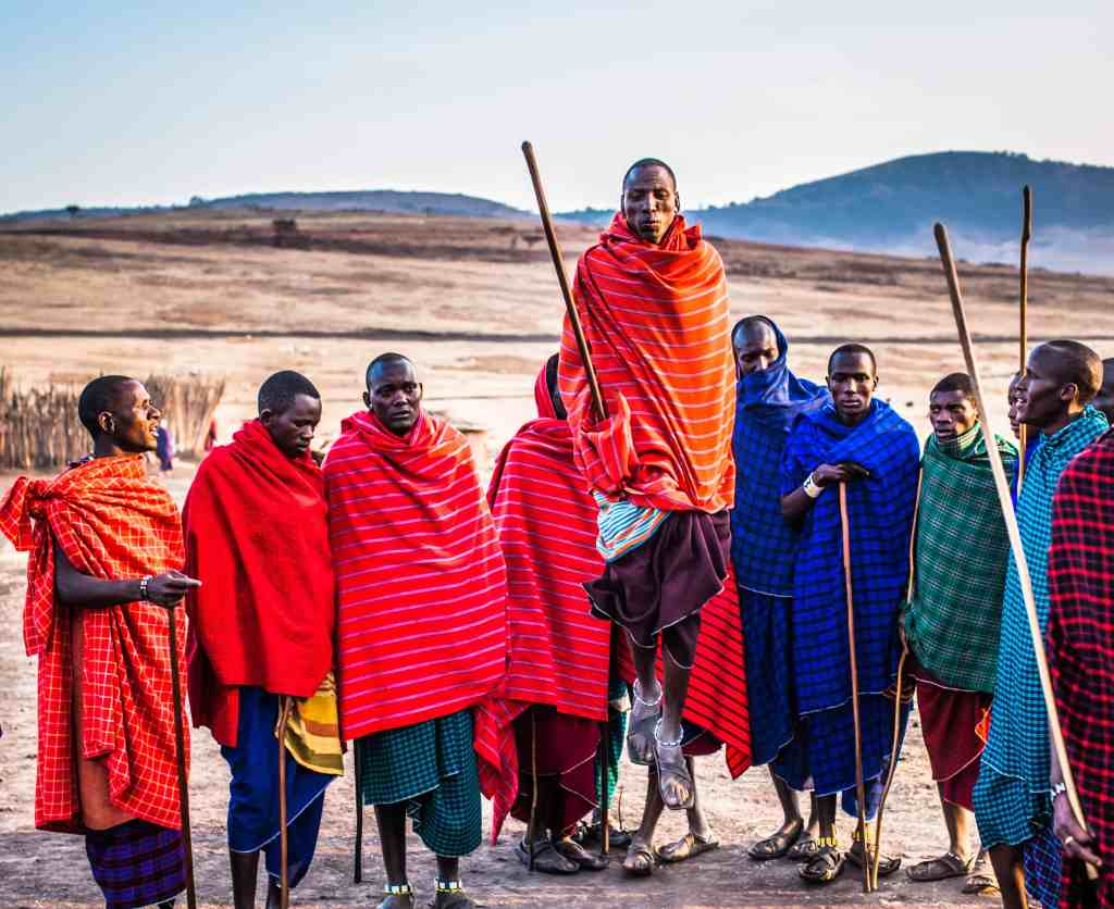 African tribe men performing dressed in colourful clothing for ethical activity.