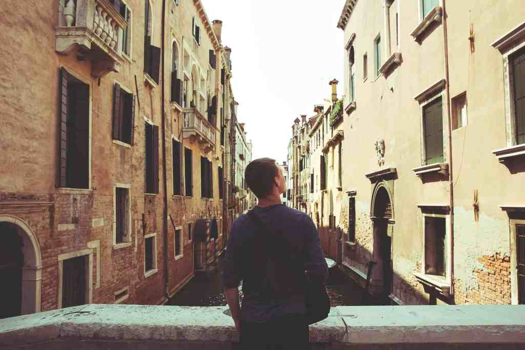 Man on a bridge looking at the buildings in Venice.