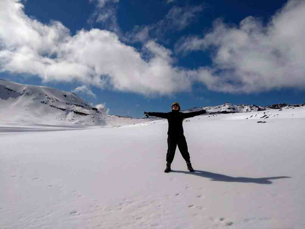 South Crater during the Tongariro Crossing. Person standing in snow with blue sky behind.