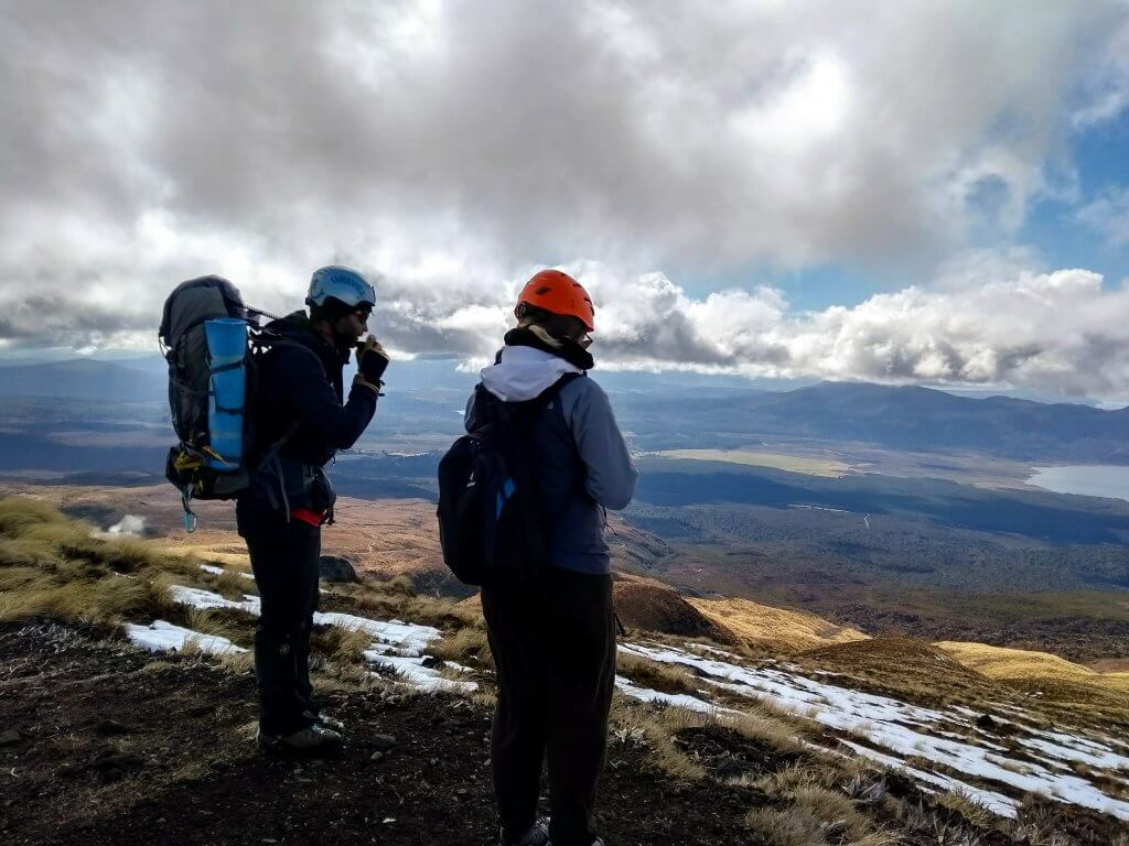 Tongariro Crossing in winter equipment for the hike. Two people wearing helmets, backpacks and jackets looking towards a valley.