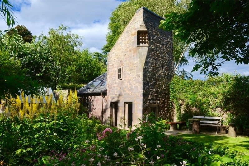 the outside of Dovecot cottage with a tower and a garden. A unique getaway in Edinburgh.