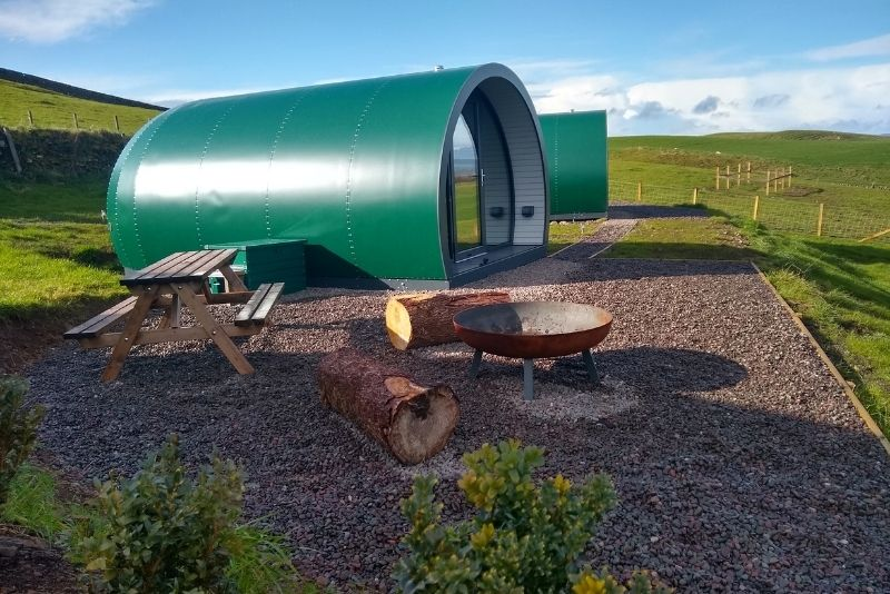 Side view of Hillhead glamping pod with an outdoor seating area. A great unique getaway in Scotland for families.