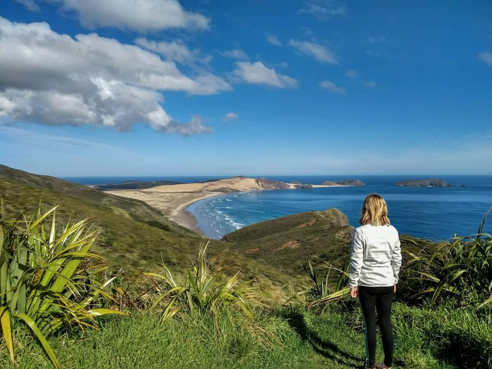 Girl standing overlooking a beach in Cape Reinga