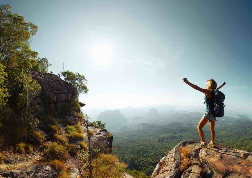 Woman standing on a rock looking at the view - these sustainable travel tips will show you how travel can be a force for good.
