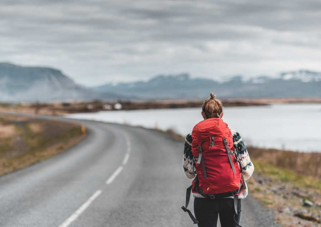 Woman wearing a red backpack walking on the road.