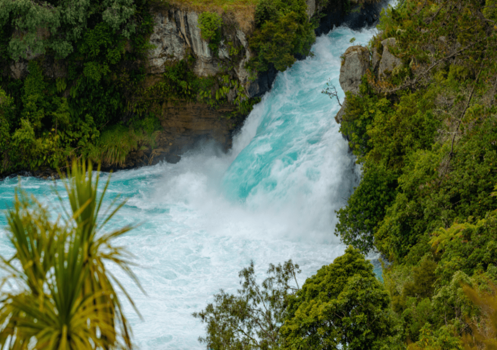 Huka Falls waterfall in Taupo. Blue water and green vegetation on New Zealand North Island itinerary.