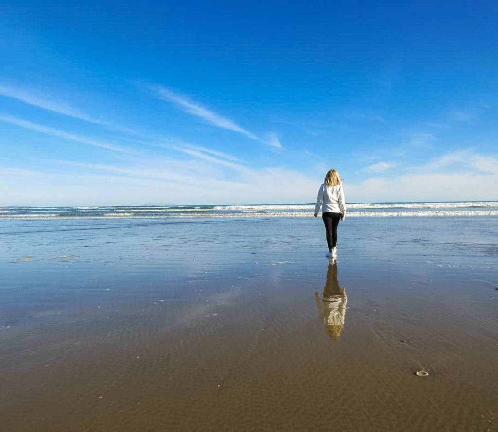 Person walking along a beach with a blue sky at 90 mile beach