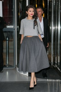 Sugar and spice and everything nice, that's what this outfit is made of. Selena toned down the glam if only for a moment to don this flirty midi skirt and crop top while in Paris. They grey scale and thick, knit fabrics gave a very cozy, fall vibe to her look, even while showing a tad bit of skin with her cropped top. The songstress even tied a little black bow in her braid for some added Parisian flair.