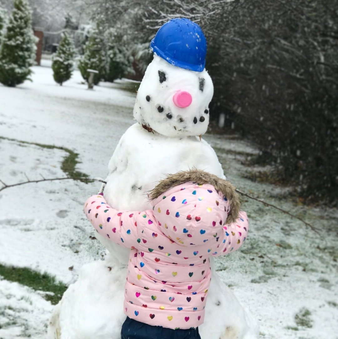 Eden hugging her first ever snowman