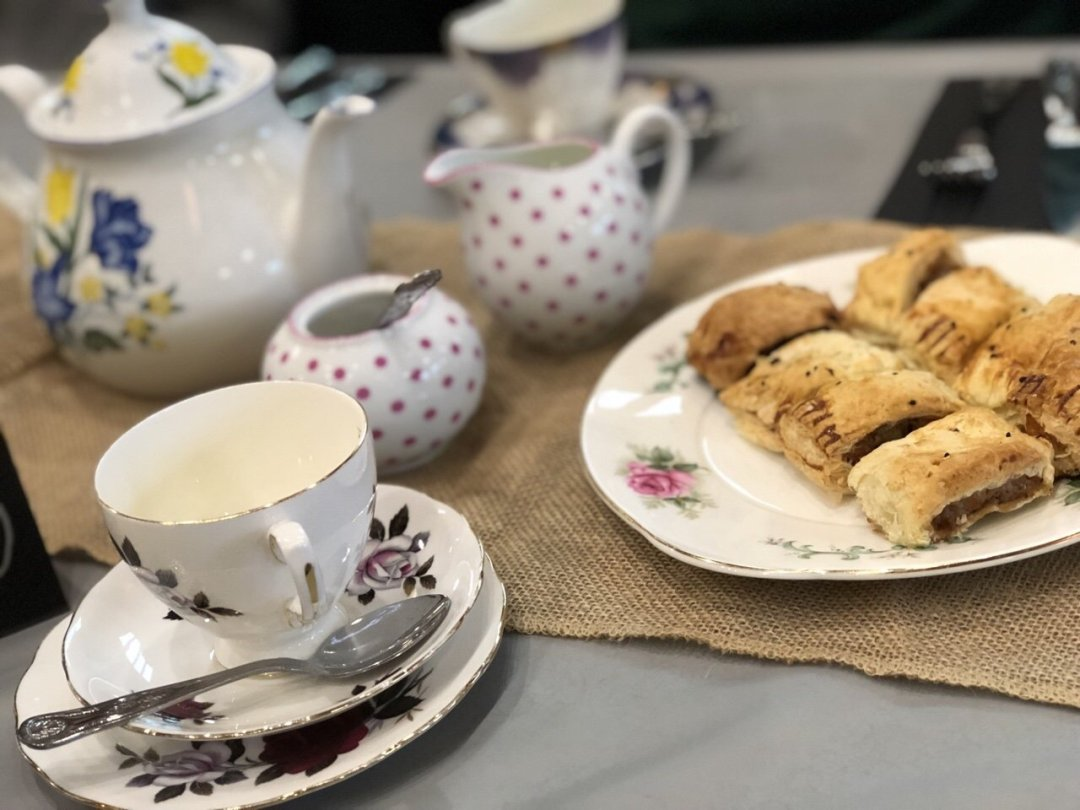 Sausage rolls and crockery set up for a magical themed afternoon tea