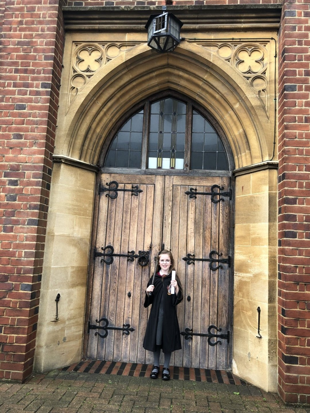 Girl standing outside the great doors at a magical themed afternoon tea